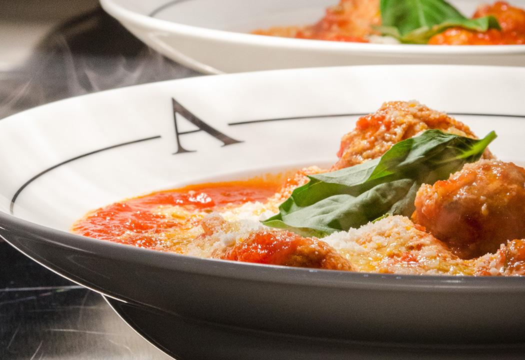 Une alléchante pizza garnie de sauce tomate, de basilic, de tomates séchées, de champignons, de roquette et de Parmigiano est découpée en 8 parts.