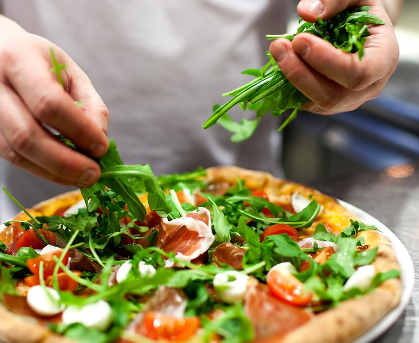 Un chef ajoute de la roquette sur une alléchante pizza Parma garnie de sauce tomate, de mozzarella et de prosciutto.